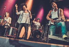 Music band performing on a stage. Multiracial music band performing on a stage Stock Image
