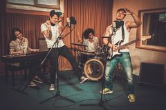 Music band performing in a studio. Multiracial music band performing in a recording studio Stock Photography