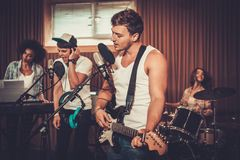 Music band performing in a studio. Multiracial music band performing in a recording studio Stock Images