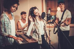 Music band performing in a studio. Multiracial music band performing in a recording studio Royalty Free Stock Image