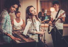 Music band performing in a studio. Multiracial music band performing in a recording studio Royalty Free Stock Images