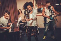 Music band performing in a studio. Multiracial music band performing in a recording studio Stock Photo