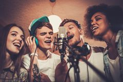 Music band performing in a studio. Multiracial music band performing in a recording studio Royalty Free Stock Photos