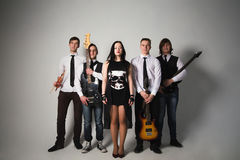 Music band in studio.Musicians and woman soloist posing over whi Royalty Free Stock Photo