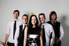 Music band in studio.Musicians and woman soloist posing over whi Stock Photos