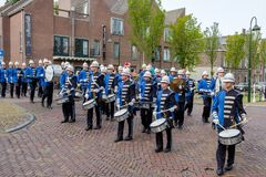 Colorful musicians in beautiful uniforms march through the streets of Delft, the Netherlands. stock image