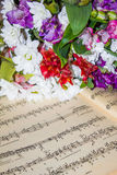 Music and beautiful flowers. A beautiful bouquet of flowers lying next to a notebook with notes of melodies Royalty Free Stock Image