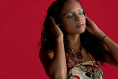 Music & Beauty in red. Pretty Girl Listening to music on her headphones Stock Photo