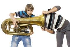 Music birth. Fun boys enjoy with a tuba Stock Images