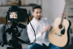 Music blogger holding and describing acoustic guitar with camera. On foreground royalty free stock photography