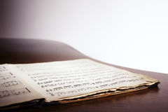 Music book on piano. Closeup of torn and yellowed music book lying on piano Stock Images