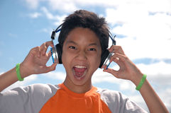 Music Boy. Boy enjoys listening to and singing music Royalty Free Stock Photos