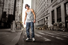 Music boy. Guy with headphones in a city street Royalty Free Stock Images