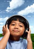 Music Boy. Young adorable boy enjoying  the universe of music he is listening from a headphone Royalty Free Stock Images