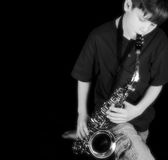 Music Boy. Inspire young musicians.  This child plays an instrument, the saxaphone.  Done in black and white Royalty Free Stock Images