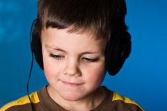 Music boy. Young boy listening to music on blue gel background Royalty Free Stock Photos