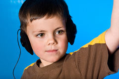 Music boy. Young boy listening to music on blue gel background Royalty Free Stock Photography