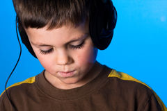 Music boy. Young boy listening to music on blue gel background Royalty Free Stock Photo