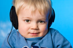 Music boy. Young boy listening to music on blue gel background Royalty Free Stock Images