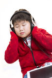 Music Boy. Vertical shot of a young Asian boy in red enjoying his moment  listening to music with a headphone isolated on white Royalty Free Stock Photography