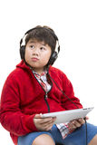 Music Boy. Vertical shot of a young Asian boy in red listening to music with a headphone isolated on white Stock Images