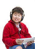 Music Boy. Vertical shot of a young Asian boy in red listening to music with a headphone isolated on white Royalty Free Stock Photo