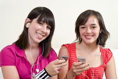 Music Break. Two friends with big smiles listening to music on their portable music players royalty free stock photography