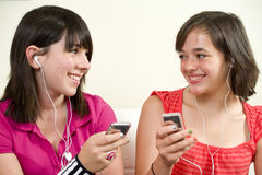 Music Break. Two friends with big smiles listening to music on their portable music players stock image