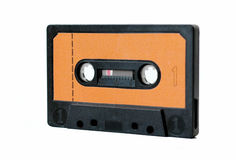 Music cassette tape. Cassette tape with orange label isolated on white Royalty Free Stock Photo