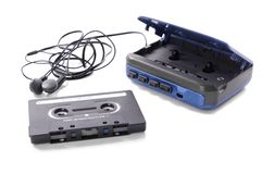 Music cassette and walkman. Old-fashioned music cassette and walkman with earphones Royalty Free Stock Photo