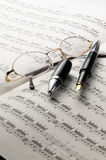 Music charts. With glasses and pen on top Royalty Free Stock Photos