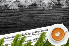 Music and Christmas decor on black wooden table with snow Royalty Free Stock Photo