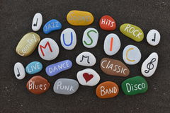 Music, cloud with many colored stones over black volcanic sand Stock Photography