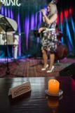A in a music club in front of a blurred stage with a burning candle and a reserved sign stock photos