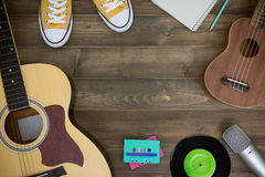 Music composer, guitar, ukulele. Wooden table of music composer, guitar, ukulele, notebook, audio cassettes, microphone, tape recorder with copy space. flat lay royalty free stock image