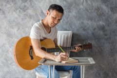 Music composing. Young man composing the song with guitar on table stock images