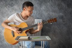 Music composing. Young man composing the song with guitar on table royalty free stock photography