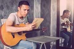Music composing. Young man composing the song with guitar on table stock photos
