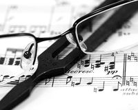Music composition. A closeup of music, tuning fork and glasses Royalty Free Stock Image
