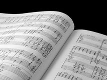 Music composition book. Musical composition pages in book against black background Stock Photo