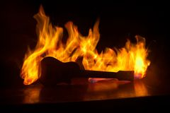 Music concept. Acoustic guitar on a dark background under beam of light with smoke with copy space. Exploding guitar. Fire effects royalty free stock photography