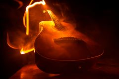 Music concept. Acoustic guitar on a dark background under beam of light with smoke with copy space. Exploding guitar. Fire effects royalty free stock photos