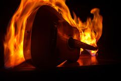 Music concept. Acoustic guitar isolated on a dark background under beam of light with smoke with copy space. Guitar Strings, close royalty free stock photography