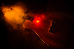 Music concept. Acoustic guitar  on a dark background under beam of light with smoke with copy space. Guitar Strings, close. Up. Selective focus. Fire effects Stock Images