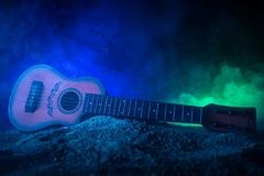 Music concept. Acoustic guitar isolated on a dark background under beam of light with smoke with copy space. Guitar Strings, close. Up. Selective focus royalty free stock photos