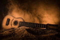Music concept. Acoustic guitar isolated on a dark background under beam of light with smoke with copy space. Guitar Strings, close. Up. Selective focus royalty free stock image