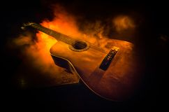 Music concept. Acoustic guitar isolated on a dark background under beam of light with smoke with copy space. Guitar Strings, close. Up. Selective focus. Fire Royalty Free Stock Photography
