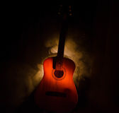 Music concept. Acoustic guitar isolated on a dark background under beam of light with smoke with copy space. Guitar Strings, close Stock Photos