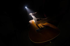 Music concept. Acoustic guitar isolated on a dark background under beam of light with smoke with copy space. Guitar Strings, close. Up. Selective focus. Fire Royalty Free Stock Images