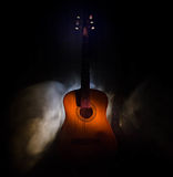 Music concept. Acoustic guitar isolated on a dark background under beam of light with smoke with copy space. Guitar Strings, close. Up. Selective focus. Fire Stock Image